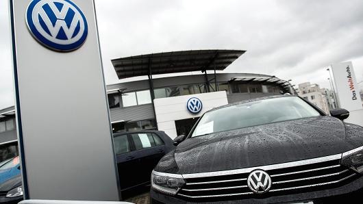 A Volkswagen AG badge sits on a Volkswagen Passat Estate automobile displayed on the forecourt of a dealership in Vienna, Austria, on Thursday, Oct. 8, 2015.