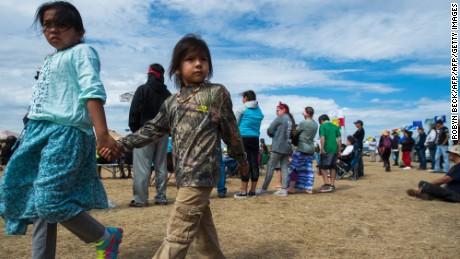 Two children walk together in oil pipeline protest encampment near Cannon Ball, North Dakota.