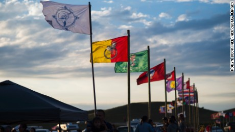 Flags of Native American tribes from across the US and Canada line the entrance of the camp.
