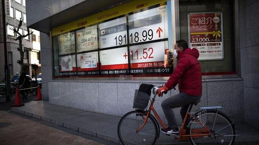 A man cycles past an electric quotation board flashing the Nikkei key index of the Tokyo Stock Exchange (TSE) in Tokyo on February 28, 2017.