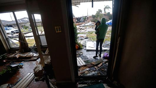 Eshon Trosclair holds her son Camron Chapital after a tornado tore through home while they were inside the New Orleans East neighborhood in New Orleans, Tuesday, Feb. 7, 2017.