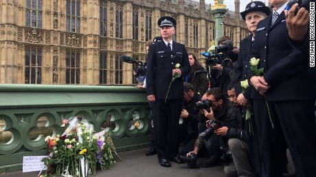 Flowers are laid at a makeshift memorial near the Houses of Parliament.