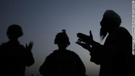 An Afghan man talks to a US Marine through an interpreter in Mian Poshteh, Afghanistan, July 14, 2009.