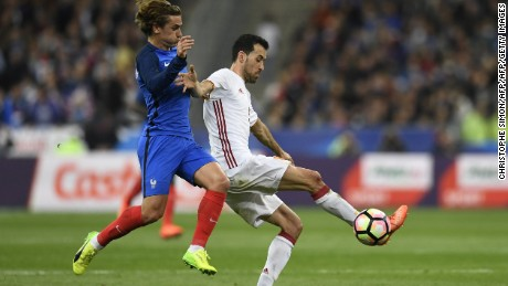 Sergio Busquets evades the challenge of France's Antoine Griezmann with a deft touch.