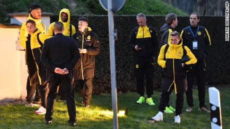 Head coach Thomas Tuchel, far right, and Borussia Dortmund players stand outside their team bus.