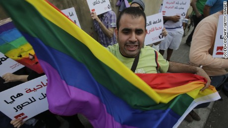 A protestor waves the gay pride flag as others hold banners during an anti-homophobia rally in Beirut on April 30, 2013.
