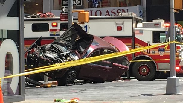A smashed car sits on the corner of Broadway and 45th Street in New York's Times Square after driving through a crowd of pedestrians