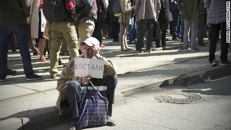 """A man carries a placard which reads: """"Fed Up."""""""