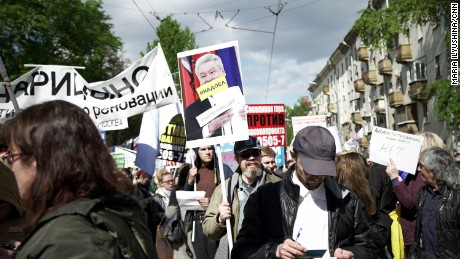 """A protester holds a sign with an image of Mayor Sergei Sobyanin and the message: """"We're tired of you."""""""