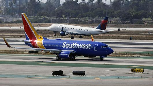 A Southwest Airlines Boeing Co. 737-700 jet taxis to Terminal 1 as a Delta Air Lines Inc. Embraer SA 175 plane lands at Los Angeles International Airport (LAX) in Los Angeles, California.