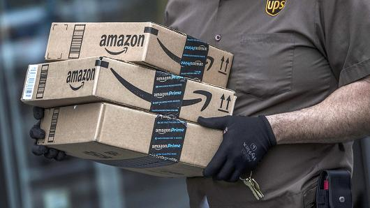 A United Parcel Service delivery driver carries Amazon.com packages in Brooklyn, N.Y.
