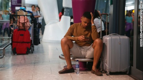 A traveler waits at Heathrow Airport Terminal 5 after British Airways flights were cancelled at Heathrow Airport.