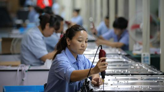 Workers assemble televisions on the production line of Tianle Group Co., Ltd on July 3, 2012 in Shengzhou of Zhejiang Province, China.