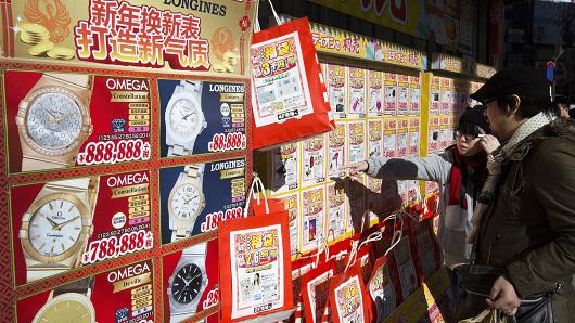 Shoppers look at 'lucky bags' containing luxury watches displayed outside a store on January 1, 2016 in Tokyo, Japan.