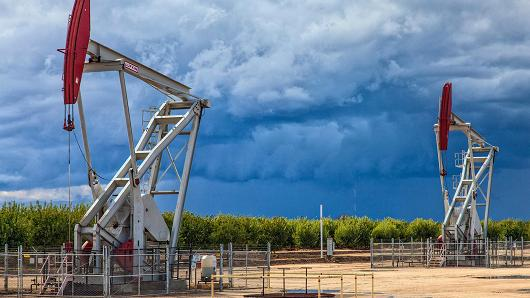 Oil well pump jacks located in Almond Orchard located over the Monterey Shale in San Joaquin Valley.
