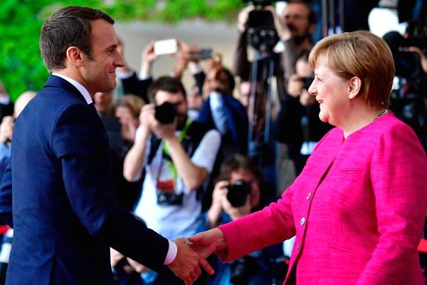 French President Emmanuel Macron (L) is greeted by German Chancellor Angela Merkel (R) prior to talks at the Chancellery in Berlin on May 15, 2017.