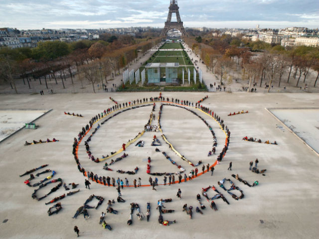Environmentalist activists form a human chain representing the peace sign and the spelling out