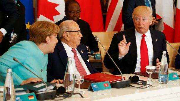 U.S. President Donald Trump talks to German Chancellor Angela Merkel (L) and Tunisia's President Beji Caid Essebsi (2-L) at the G7 Summit expanded session in Taormina, Sicily, Italy May 27, 2017. REUTERS/Jonathan Ernst - RTX37U3O