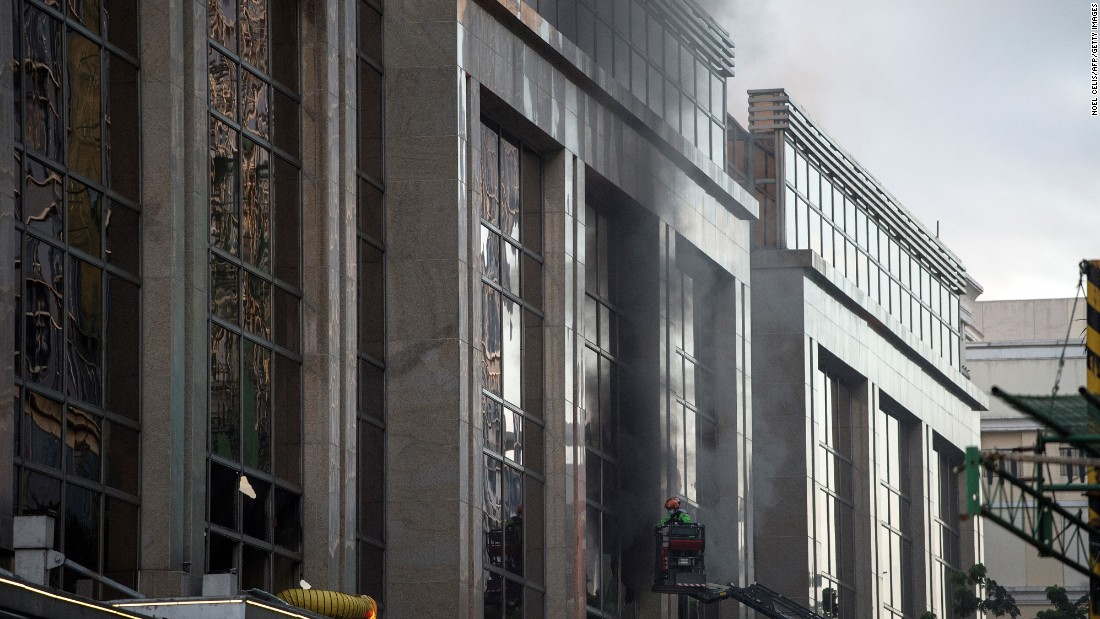Firemen break a glass window of the Resorts World Hotel following the assault.