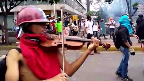 He played on amidst the chaos of protests - until cops broke his violin
