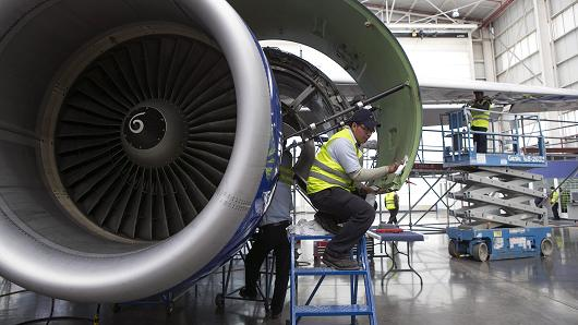 Employees work on the engine of a jet at the Interjet maintenance hangar in Toluca, Mexico.