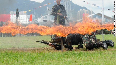 PLA soldiers crawl under a burning frame during a demonstration at the open day of the Chinese People's Liberation Army (PLA) Navy Base at Stonecutter Island in Hong Kong on July 1, 2016.