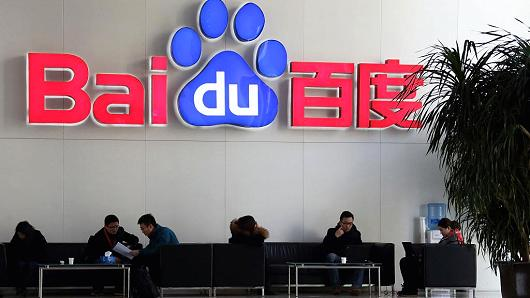 Visitors sit on sofas below the Baidu logo in the reception area of the company's headquarters in Beijing, China.