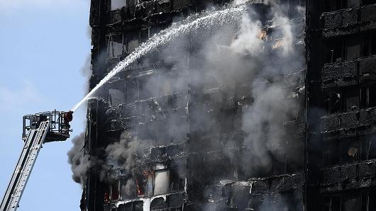 Fire fighters drench the burning 24-storey residential Grenfell Tower block on June 14, 2017 in London, England.