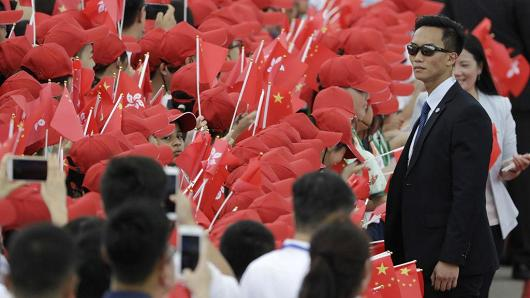 A security official stands in front of attendees waving China and Hong Kong flags ahead of Chinese President Xi Jinping's arrival at Hong Kong International Airport on June 29, 2017.