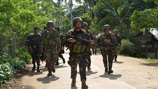 This photo taken on August 26, 2016 shows Philippine soldiers walking along a highway as they return to camp at the village of Bongkaong, Patikul town, Sulu province on the southern island of Mindanao.