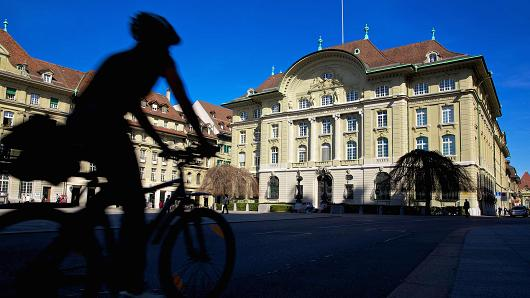 A cyclist rides past the Swiss National Bank's headquarters in Bern, Switzerland.