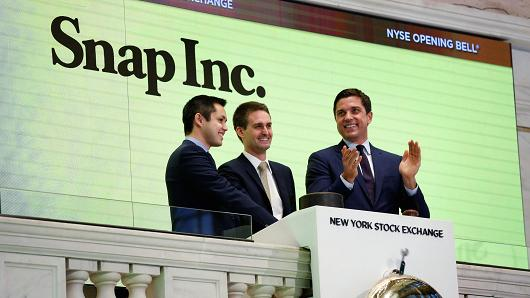 Snap cofounders Evan Spiegel (C) and Bobby Murphy ring the opening bell of the New York Stock Exchange (NYSE) with NYSE Group President Thomas Farley shortly before the company's IPO in New York, U.S., March 2, 2017.
