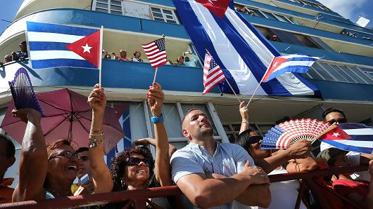 Hundreds of Cubans and visitors from other countries gather across the street from the newly reopened U.S. Embassy to observe the flag-raising ceremony August 14, 2015 in Havana, Cuba.