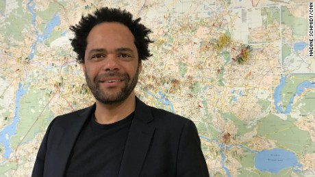 """Eben Louw, a psychologist at an anti-violence aid group in Berlin. The map behind him shows all the attacks on refugees and migrants recorded in the city. """"What is new is the level of brazenness."""""""