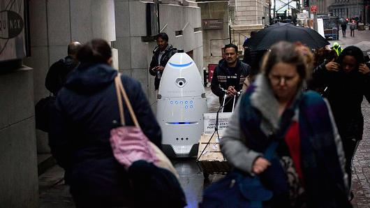 Pedestrians pass a Knightscope K5 security robot on Wall Street, New York, on January 17, 2017.