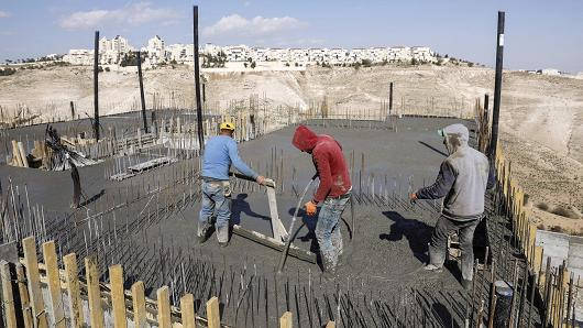 Palestinian labourers work at a construction site in a new housing project in the Israeli settlement of Maale Adumim, east of Jerusalem, on January 22, 2017.