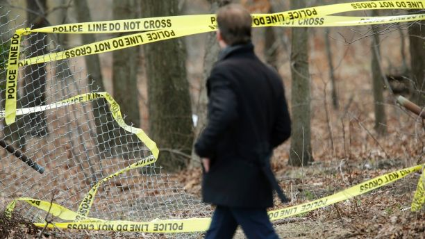 A man walks past police tape near a crime scene in Central Islip, N.Y., Thursday, April 13, 2017. Police say the bodies of four apparent homicide victims have been found in a Long Island park. The victims were found in a wooded area near a recreation center in Central Islip. (AP Photo/Seth Wenig)