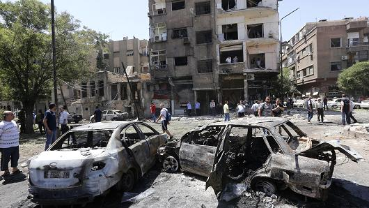 Charred vehicles are seen on the site of a suicide bomb attack in the Syrian capital's eastern Tahrir Square district, on July 2, 2017.