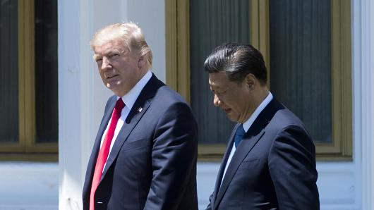 President Donald Trump (L) and Chinese President Xi Jinping (R) walk together at the Mar-a-Lago estate in West Palm Beach, Florida, April 7, 2017.