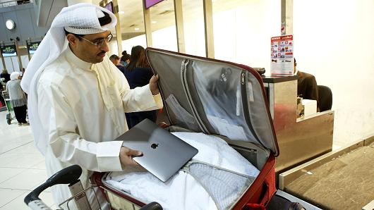 Kuwaiti social media activist Thamer al-Dakheel Bourashed puts his laptop inside his suitcase at Kuwait International Airport in Kuwait City before boarding a flight to the United States on March 23, 2017.
