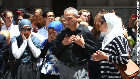 Muslim community leader Dr Jamal Rifi and family members lay a wreath at the makeshift memorial at Martin Place after the 2014 shootings at the Lindt coffee shop in Sydney's Martin Place. Sydney Australia.