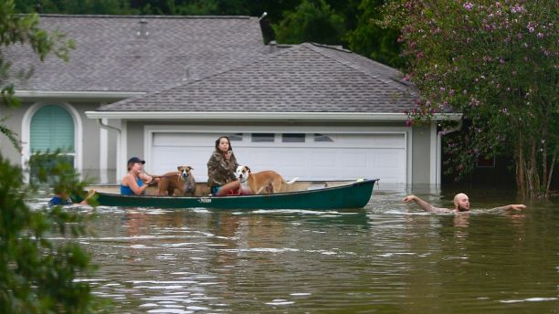 A family evacuates their Meyerland home in Houston, Sunday, Aug. 27, 2017.  Rescuers answered hundreds of calls for help Sunday as floodwaters from the remnants of Hurricane Harvey rose high enough to begin filling second-story homes, and authorities urged stranded families to seek refuge on their rooftops.  (Mark Mulligan/Houston Chronicle via AP)