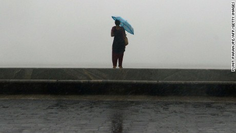 Heavy rainfall caused chaos in the coastal city (above). A woman is seen (below) on the sea front during the heavy rain showers on Tuesday.