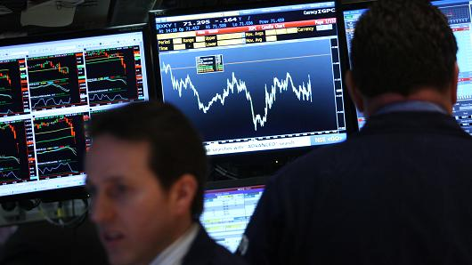 A stock chart is displayed on a terminal as traders work on the floor of the New York Stock Exchange.