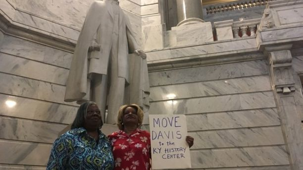 Charlene Holloway, right, and Gracie Lewis stand in front of a statue of Jefferson Davis in the Kentucky Capitol on Wednesday, Aug. 30, 2017. The women were some of the more than 100 people who attended a rally on calling for the statue's removal. Holloway says she is the descendant of a black slave and her white owner. (AP Photo/Adam Beam)