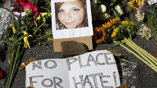 A makeshift memorial of flowers and a photo of the victim of the car attack is on display at the attack site  in Charlottesville, Va., Sunday, Aug. 13, 2017.