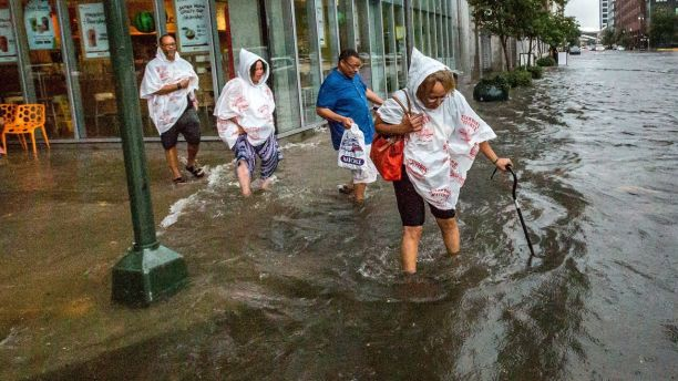 CORRECTS CREDIT TO THE ADVOCATE - In this Saturday, Aug. 5, 2017, photo, Philana Crite, of Cleveland who was in town for a family reunion, steps of the curb into flood waters in the New Orleans. Parts of New Orleans flooded after a heavy weekend rainfall that officials said overwhelmed the city's pump stations. (Scott Threlkeld/The Advocate via AP)
