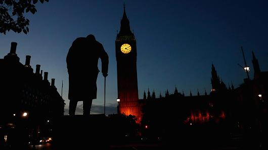 Dawn breaks behind the Houses of Parliament and the statue of Winston Churchill in Westminster, London, Britain June 24, 2016.