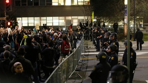 Protesters chant in front of a police line outside Berkley Police Department headquarters during a march against the New York City grand jury decision to not indict in the death of Eric Garner in Berkeley, California December 9, 2014. Cities across the United States have seen large protests in recent nights following a grand jury's decision not to charge an officer in the July killing of Eric Garner. An unarmed black father of six, Garner died after police put him in a banned chokehold.  REUTERS/Stephen Lam (UNITED STATES - Tags: POLITICS CIVIL UNREST) - GM1EACA1GVD01