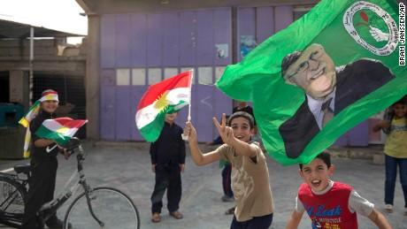 Children holding Kurdish flags run through the streets of Kirkuk on Monday.